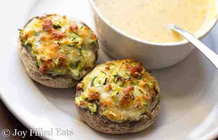 Cheese Stuffed Mushrooms with Bacon on a white plate with a bowl of creamy orange soup in the background