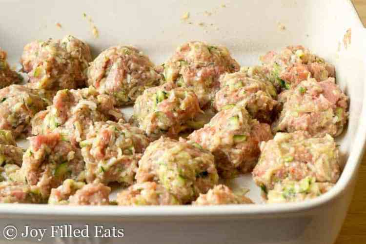 The meatballs for the meatball casserole in a large baking dish ready to go into the oven