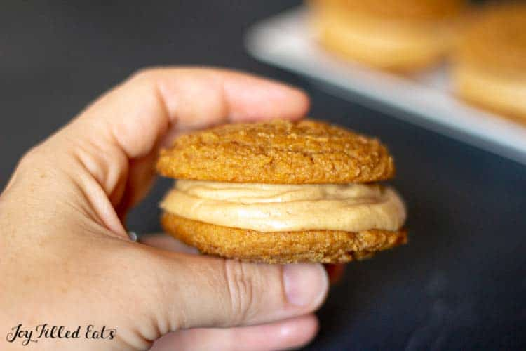 a hand holding up a peanut butter whoopie pie
