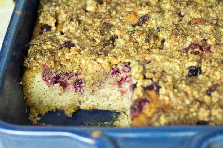 Baked Cranberry Cake in a blue baking dish with a piece missing