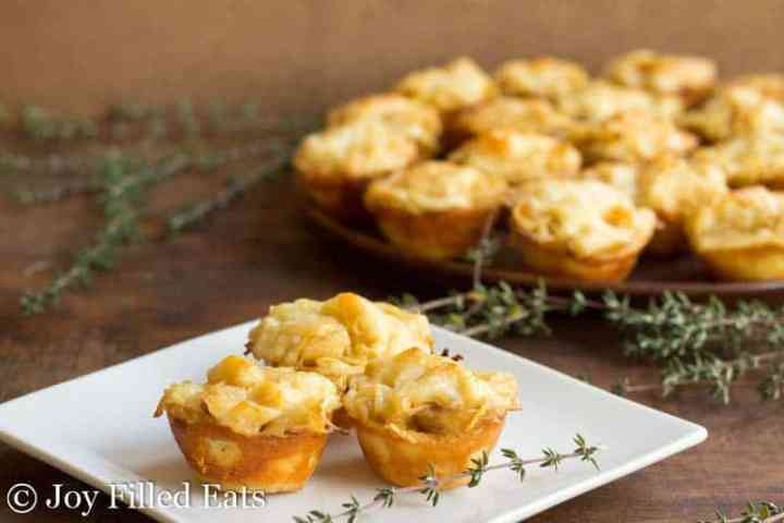 Onion Tartlets on a white plate with a sprig of fresh thyme