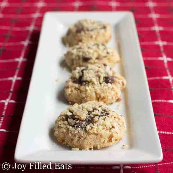 Almond Crunch Chocolate Thumbprint Cookies lined up on a white rectangular serving tray
