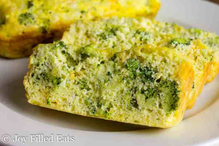 Slices of the broccoli & cheddar keto breakfast bread recipe on a white plate.