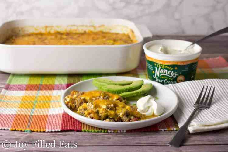 Easy Taco Casserole Recipe served on a white plate with sour cream and avocado