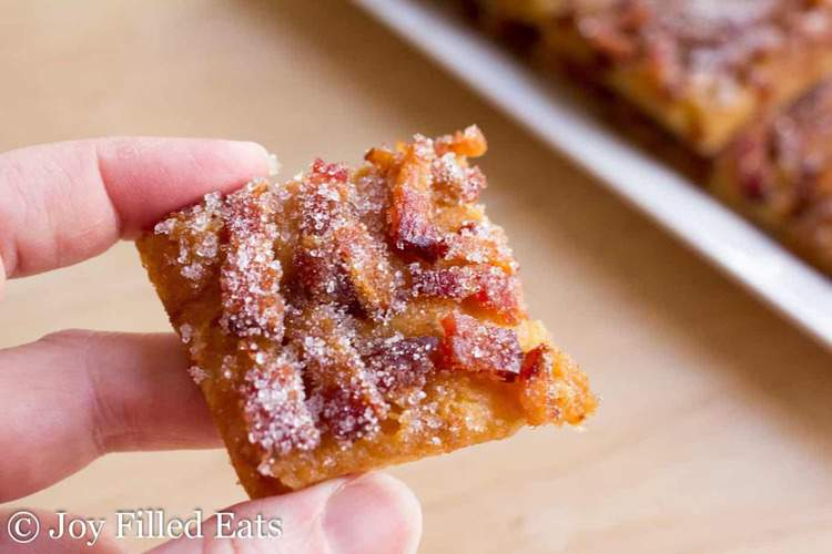 hand holding a piece of bacon covered pastry