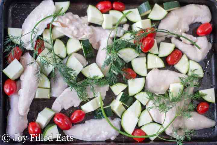 sheet pan with frozen chicken tenders, zucchini, tomatoes, and dill