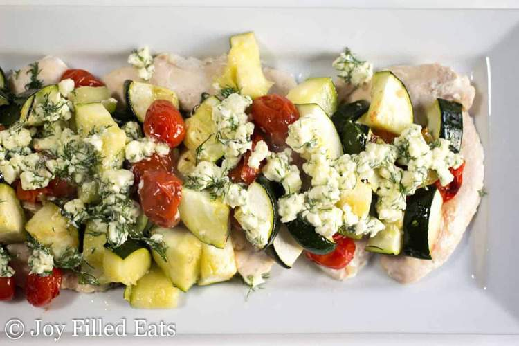 baked greek chicken with feta and dill on a white platter