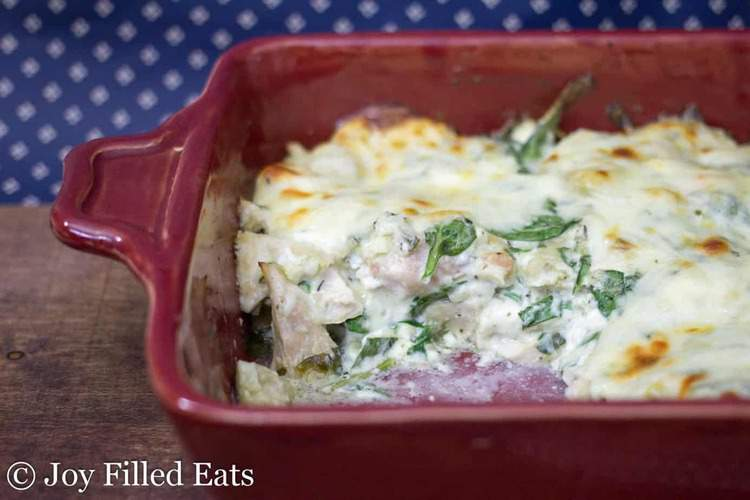 Spinach & Artichoke Chicken Casserole in a red casserole dish with a scoop missing. You can see the chicken and spinach with golden cheese on top.