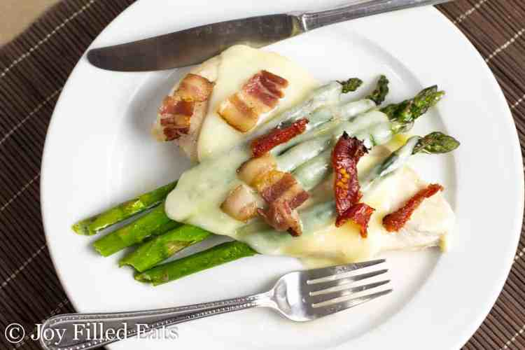 a plate with baked chicken asparagus bacon and sundried tomatoes topped with cheese