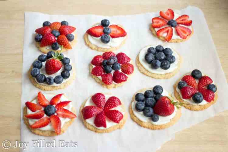 The healthy fruit pizza cookies covered with berries on parchment