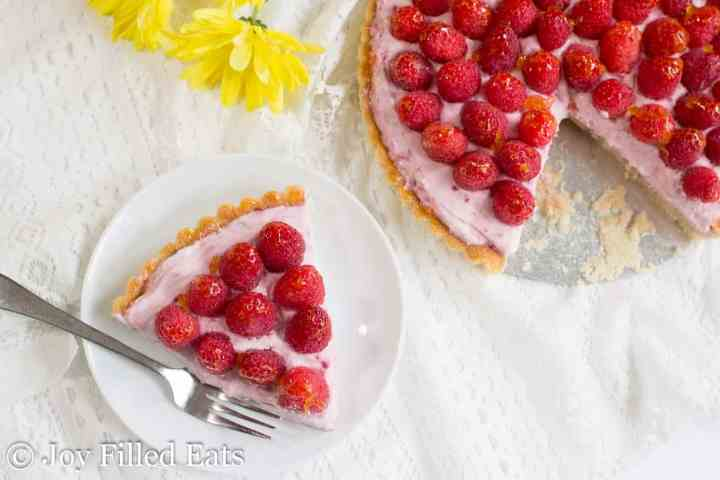 overhead view of a slice of raspberry mousse tart on a white plate with the rest of the tart next to it