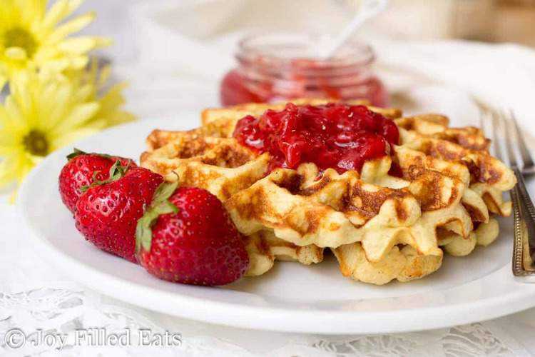 Vanilla Waffles with Almond Flour on a white plate with strawberries and jam