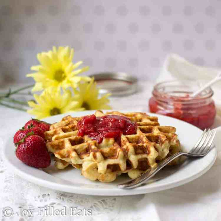 The Classic Vanilla Waffles with Almond flour on a plate with a dollop of jam and some fresh berries