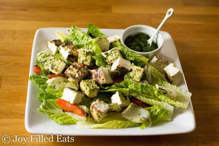 Grilled Paneer Salad and cilantro-mint chutney on a white square plate