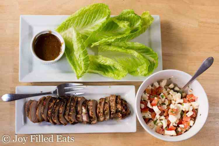 a plate with lettuce and balsamic dressing, one with sliced grilled pork tenderloin, and a bowl of caprese salad