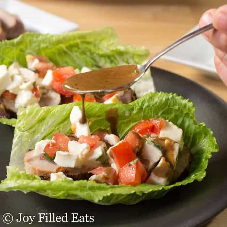 a hand drizzling balsamic dressing over a grilled pork tenderloin lettuce wrap with caprese salad