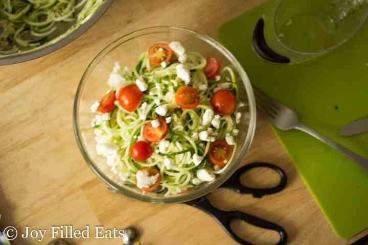 overhead shot of the zucchini salad in a bowl with a scissors, fork, and measuring cup