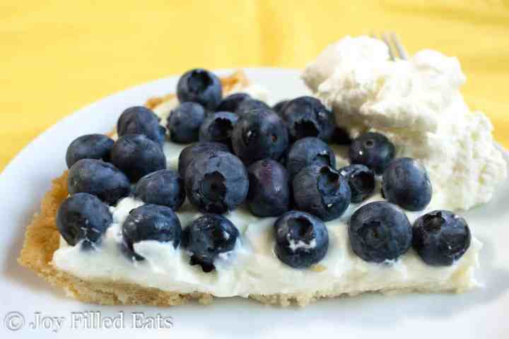 Lemon Ricotta Pie on a white plate topped with blueberries and whipped cream