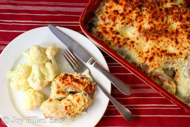 two pieces of Baked Sausage with Creamy Basil Sauce on a white plate with cauliflower
