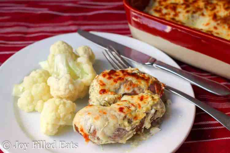 Baked Sausage with Creamy Basil Sauce on a plate with a red casserole dish behind