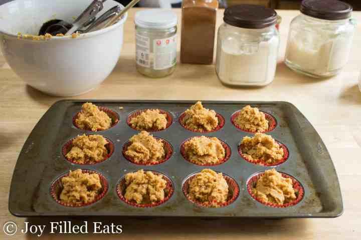 pumpkin muffin batter scooped into a muffin tin