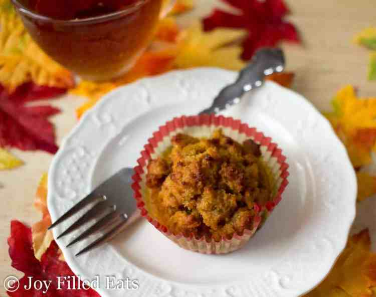 one of the Easy Pumpkin Muffins on a plate next to a cup of tea