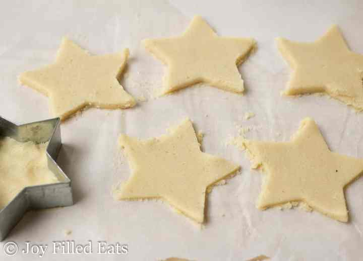cookie dough shaped like stars on parchment paper