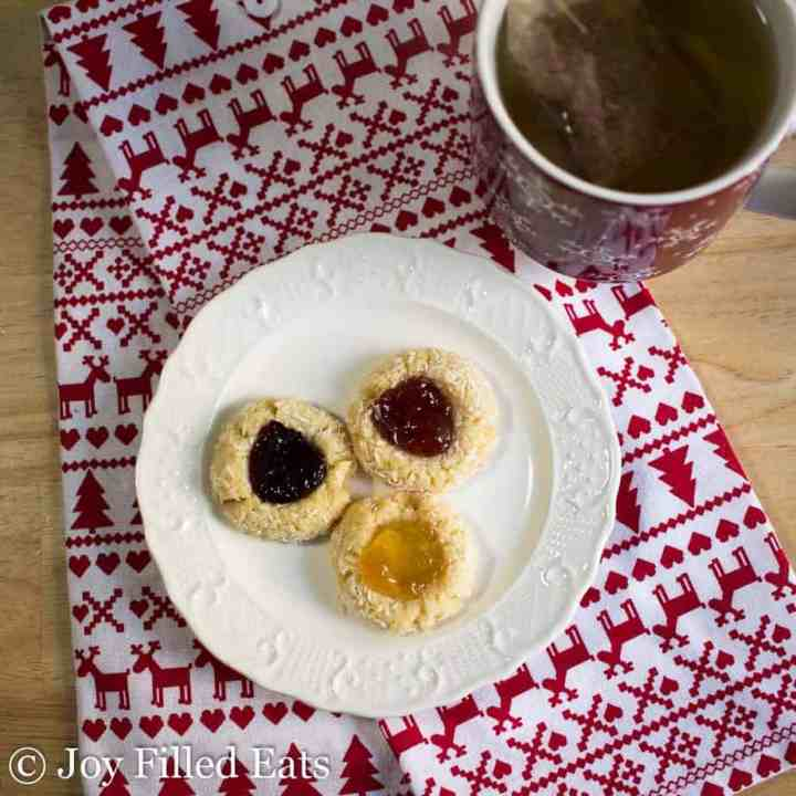 Jam Thumbprint Low Carb Cookies on a white plate with a cup of tea