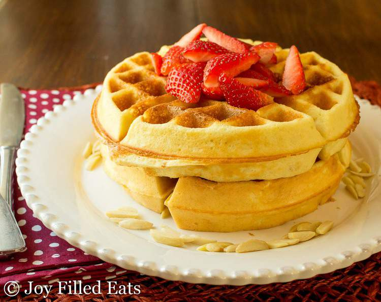 A stack of strawberry topped Easy Flourless Almond Low Carb Waffles.