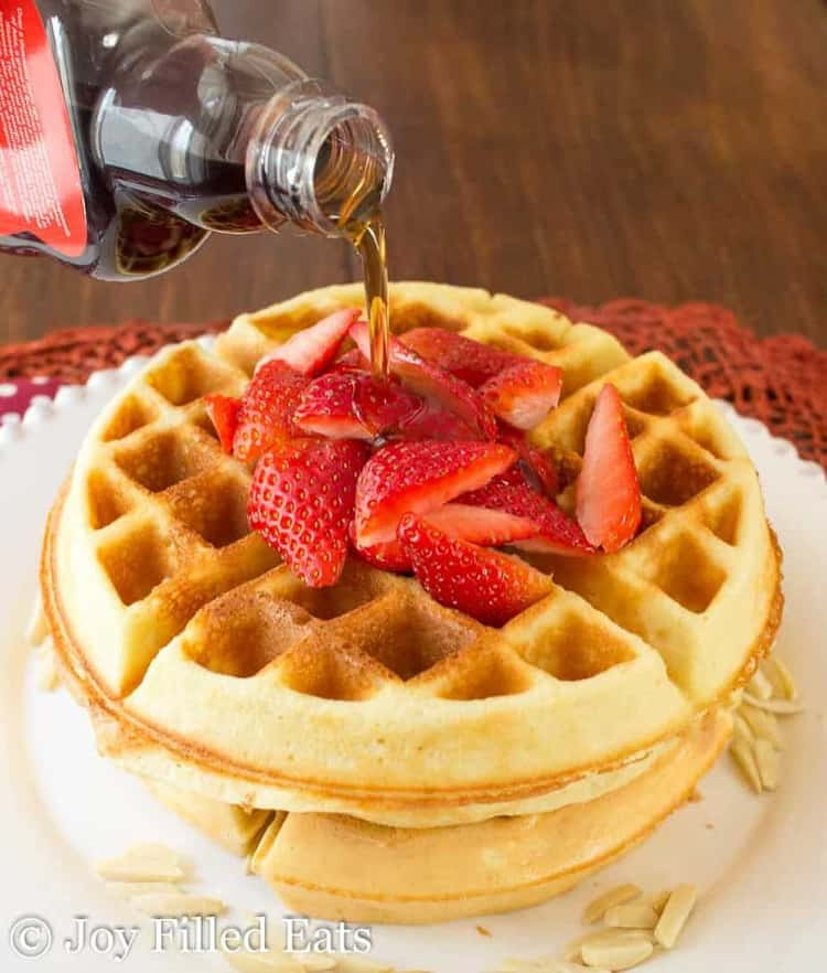 Syrup being poured over 2 strawberry topped low carb waffles.