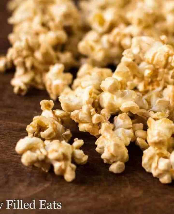 Close up of caramel popcorn on a dark wood cutting board.