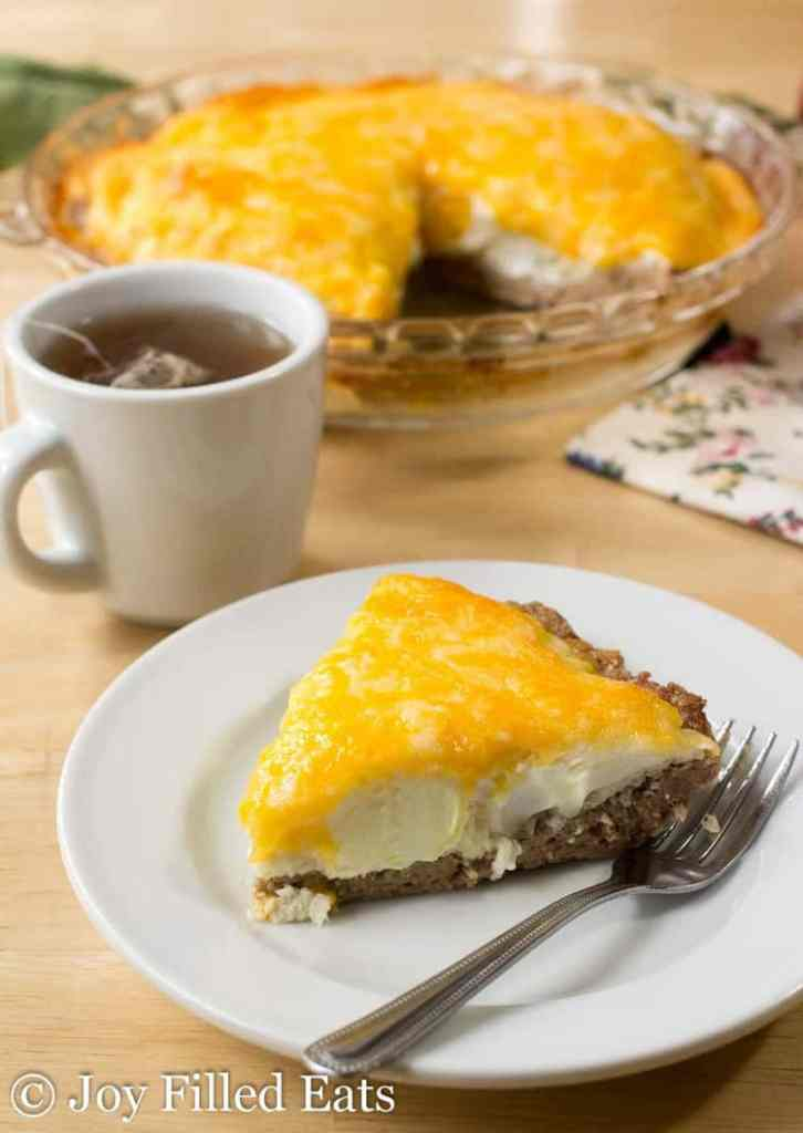 A white plate with a slice of the egg & sausage pie. The rest of the pie is in the background.
