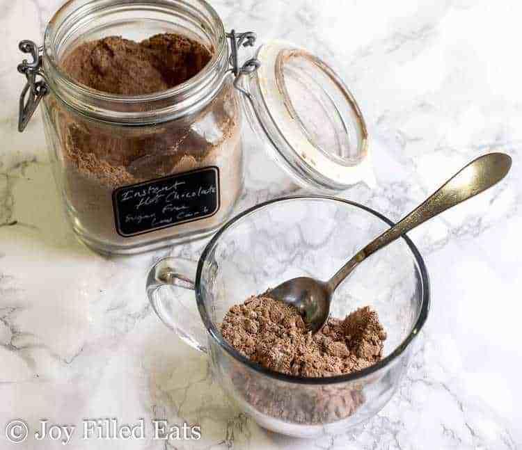 Jar of Sugar Free Hot Chocolate Mix. Mug with mix and a spoon.