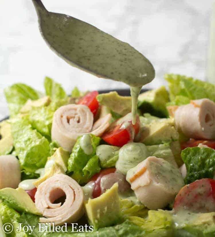A spoon drizzling the paleo ranch dressing on top of a salad of lettuce, tomatoes, avocado, and turkey.