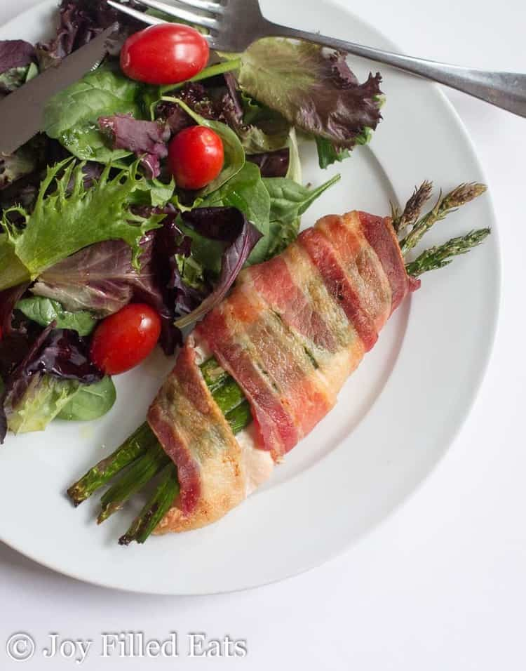 Stuffed Chicken with Asparagus & Bacon on a white plate with a side salad