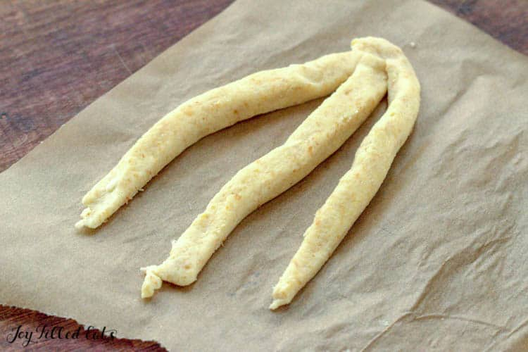 three strips of dough connected at the top to braid