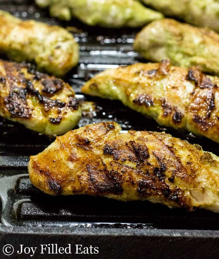 cooked cilantro lime marinated chicken tenderloins with grill lines on a grill pan