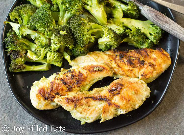 Cooked chicken tenderloins that were marinated in the Cilantro Lime Chicken Marinade on a black plate with broccoli