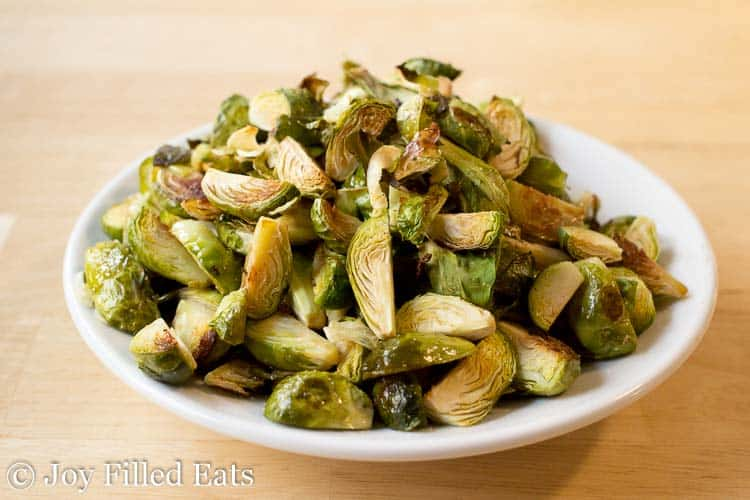 Roasted Brussels Sprouts with Garlic piled high in a white serving bowl