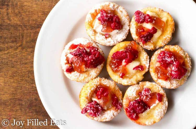 Seven of the Brie Appetizer Bites with Raspberry topping on a white plate