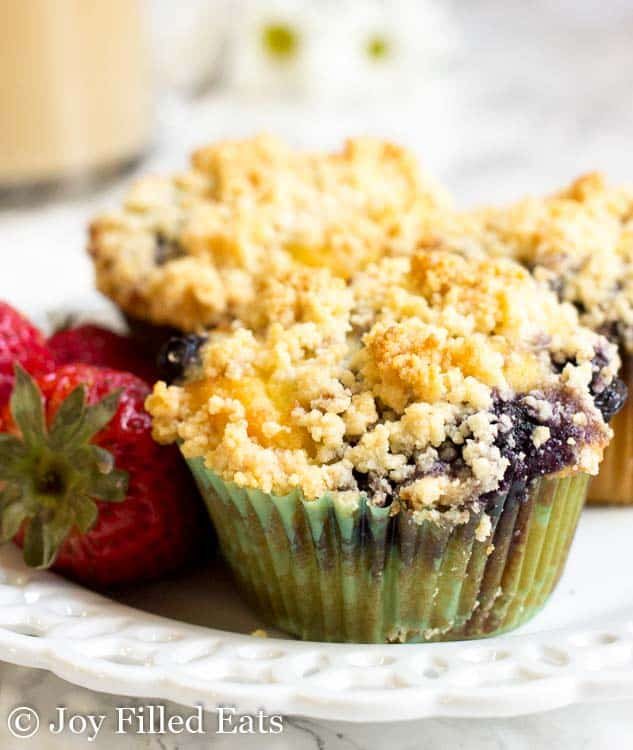 A white plate with 3 blueberry muffins with crumb topping and some strawberries