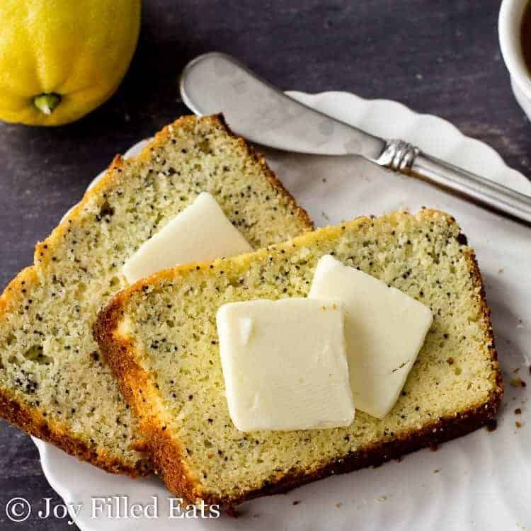 slices of the poppyseed cake with pats of butter on a white plate