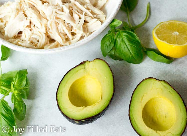 An avocado cut in half with fresh basil and lemons