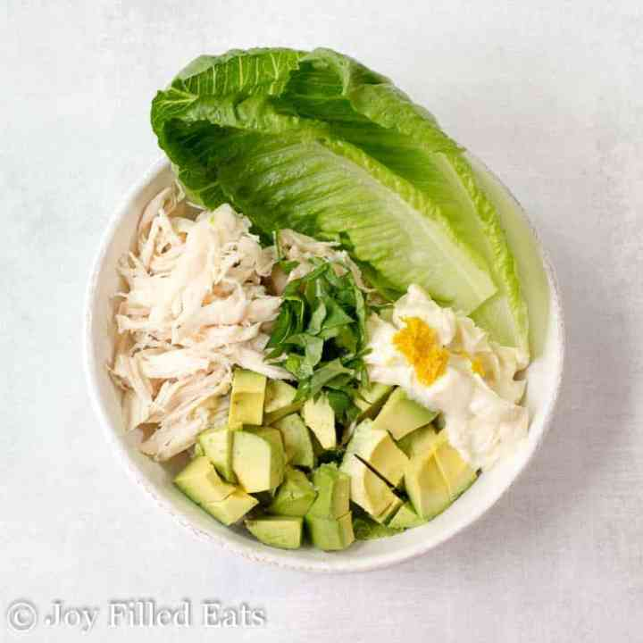 A bowl with the ingredients for the best chicken salad with avocado