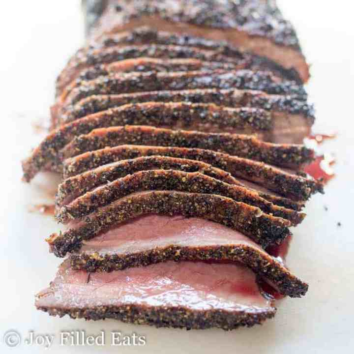 Meat slices on a cutting board showing off this London broil recipe for the grill