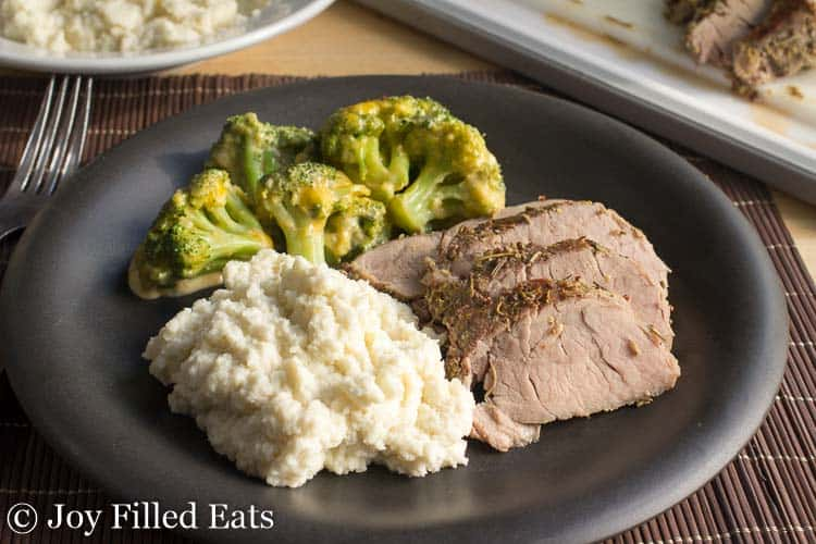 A black plate with Sous Vide Pork Tenderloin, mashed cauliflower, and broccoli