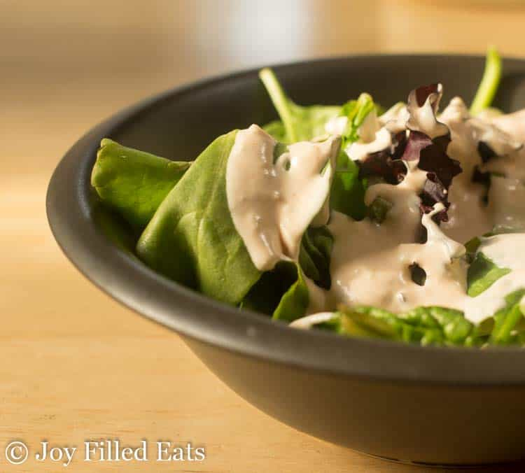 A black bowl with mixed greens and dressing from the Creamy Garlic Salad Dressing Recipe