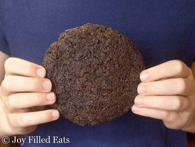 a child's hands holding a huge chocolate cookie from the Triple Chocolate Cookies Recipe