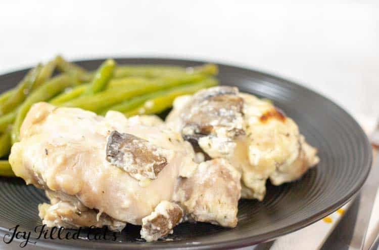 baked boneless chicken thighs with mushrooms on a black plate