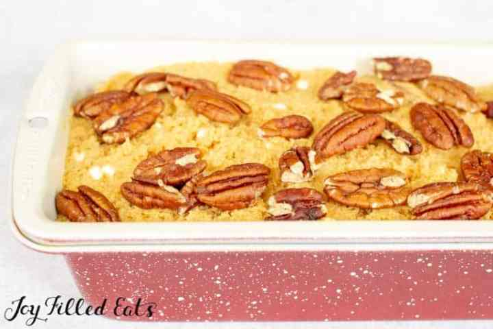 A white and red speckled loaf pan with the raw pumpkin bread batter and pecan topping